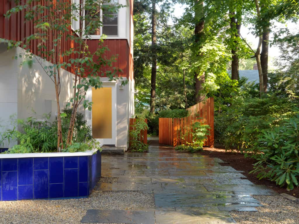 Tiled planter, bluestone pavers, custom fence. Landscape design by JMMDS, Photograph by Susan Teare