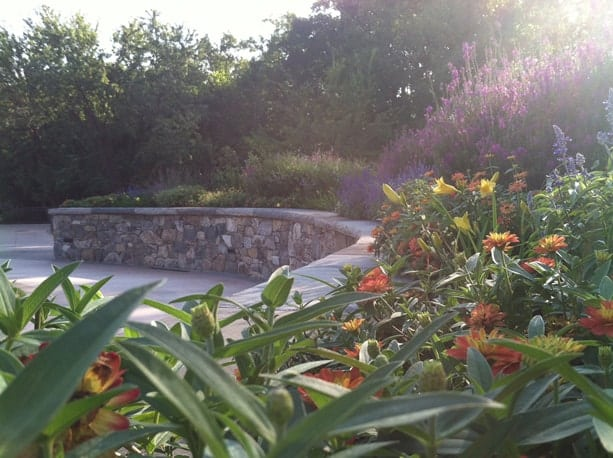 Colorful planting beds are contained by bench-topped stone walls.