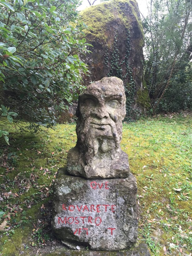 Bust of old man with massive stone behind.