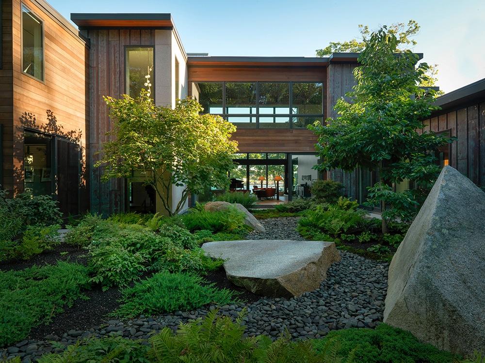 JMMDS-landscape-architecture-maine-coast-sliding-window-wall-boulder-riverstone-garden-living-room-inside-out